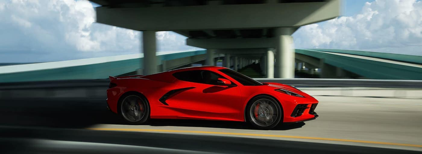 A red 2021 Chevy Corvette Stingray is driving under a highway overpass.
