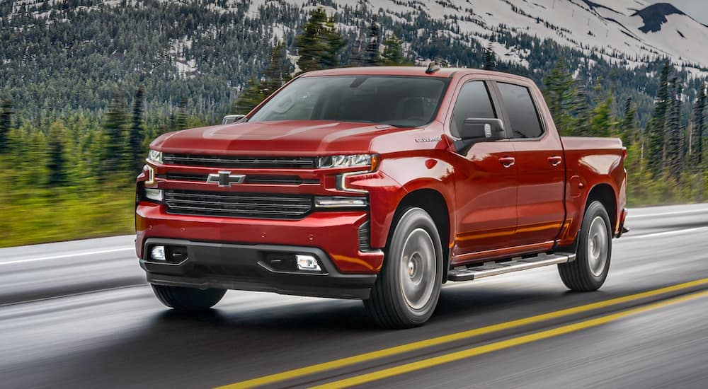A red 2021 Chevy Silverado is driving past a mountain.