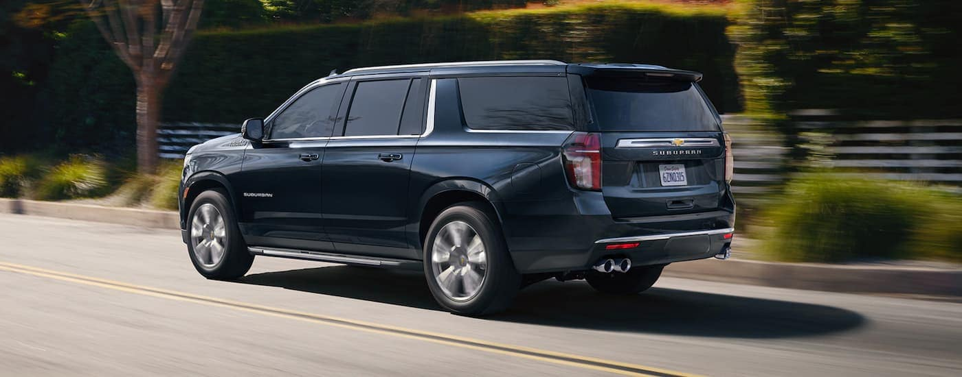A blue 2021 Chevy Suburban is driving on a suburban street after leaving a Chevy dealer in Allentown, PA.