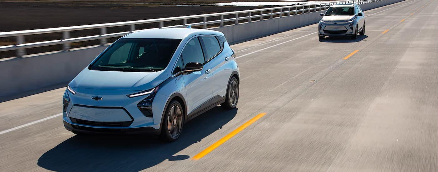 A pale blue 2022 Chevy Bolt EV and tan EUV are shown driving over a highway bridge.