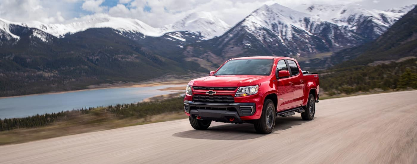 A red 2022 Chevy Colorado Trailboss is shown driving past a lake and mountains.