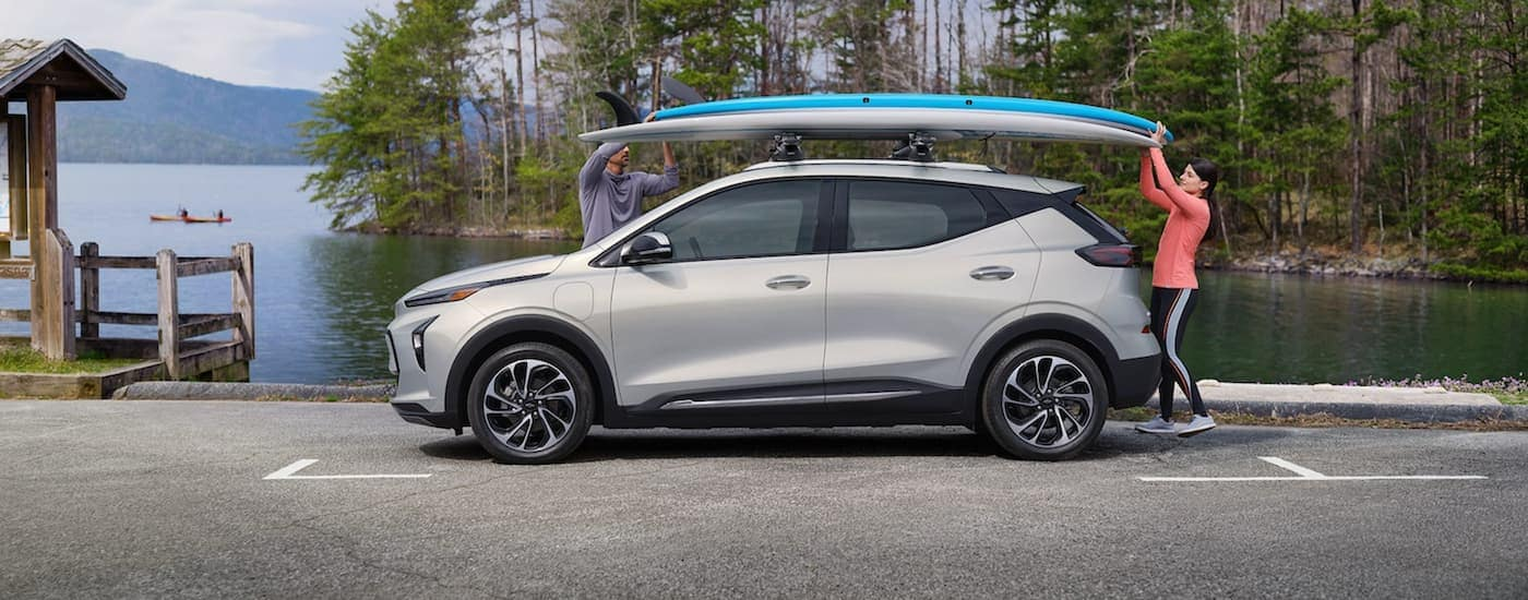 A silver 2022 Chevy Bolt EUV is shwon from the side in front of a lake while a couple gets paddle boards off the roof.