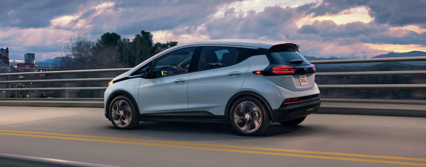 A light blue 2022 Chevy Bolt EV is driving on a highway at sunset.