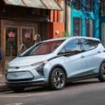 A baby blue 2022 Chevy Bolt EV is parked on a city street after leaving a Pennsylvania electric car dealer.