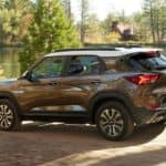 A bronze 2022 Chevy Trailblazer is shown from the side driving past a lake after leaving a Chevy dealer in Allentown, PA.