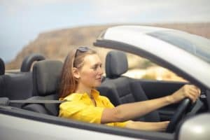 woman-in-yellow-shirt-driving-a-silver-car
