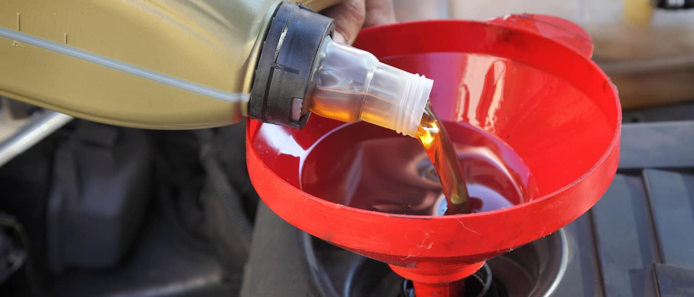 oil change being poured into into funnel