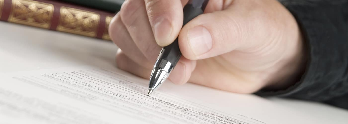 man signing papers for insurance