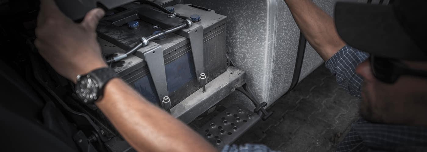 certified mechanic checking semi truck battery