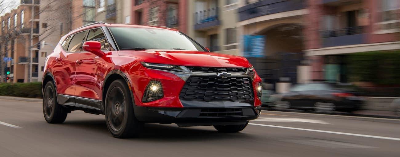 A red 2019 Chevy Blazer RS is driving down a town street near Buford, GA.