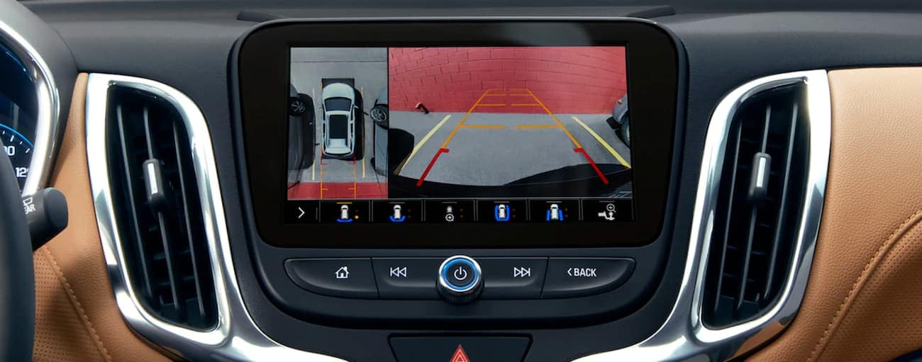 The 2019 Chevy Equinox has backup camera footage displayed on the screen.