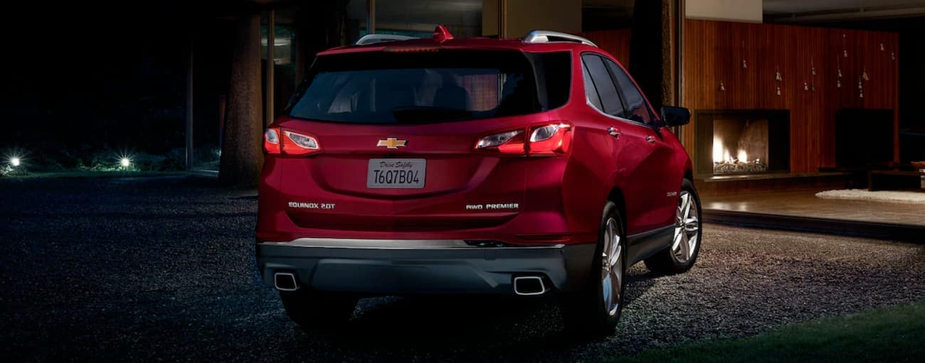 A red 2019 Chevy Equinox Premier is shown at night outside a modern house near Buford, GA.