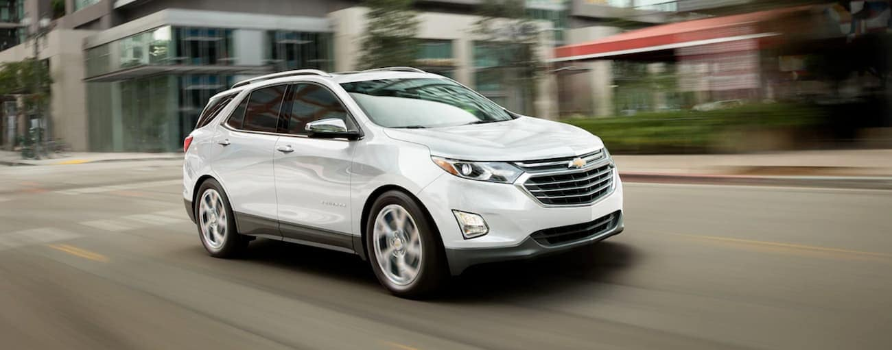 A white 2019 Chevy Equinox is driving past buildings outside Buford, GA.
