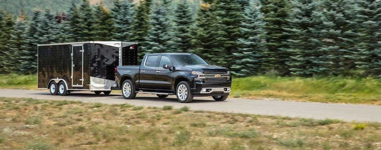 A black 2019 Chevy Silverado 1500 is towing an enclosed black trailer.