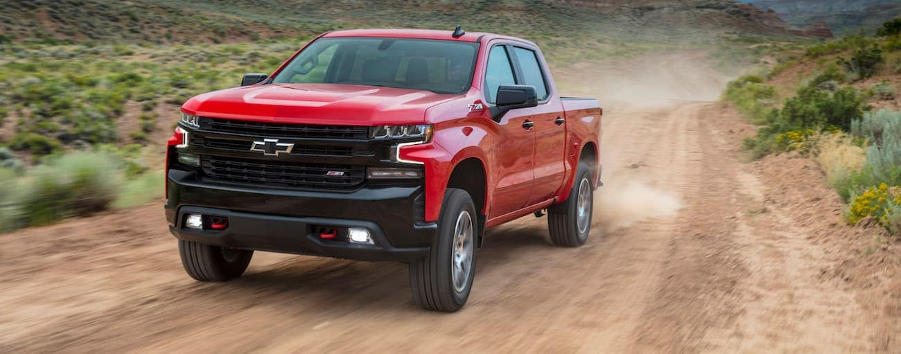 A red 2019 Chevy Silverado 1500 with black trim is driving on a dirt road outside Buford, GA.