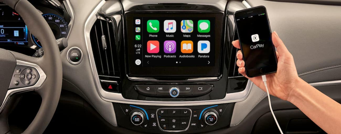 A phone with the Apple CarPlay feature is shown in the interior of a 2019 Chevy Traverse.