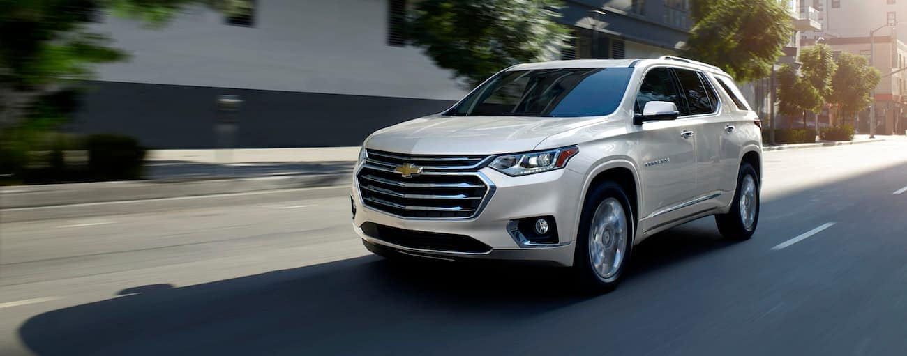 A white 2019 2019 Chevy Traverse is driving past buildings.