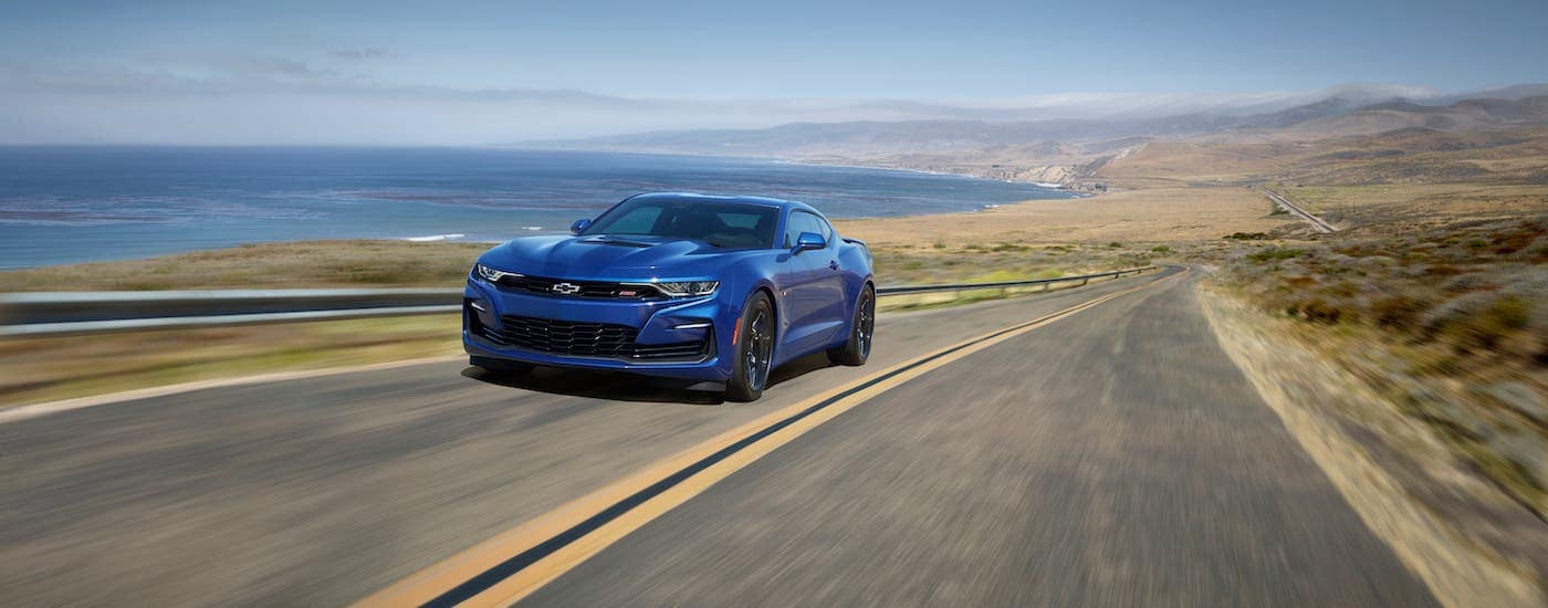 A blue 2020 Chevy Camaro SS from a Chevy dealer is driving along an ocean-side highway.