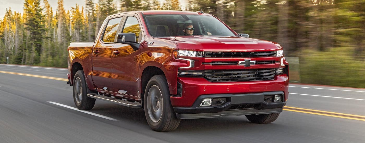 A red 2020 Chevy Silverado is driving on a tree-lined highway.