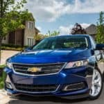 A blue 2016 Chevy Impala is parked in front of a house in a neighborhood.