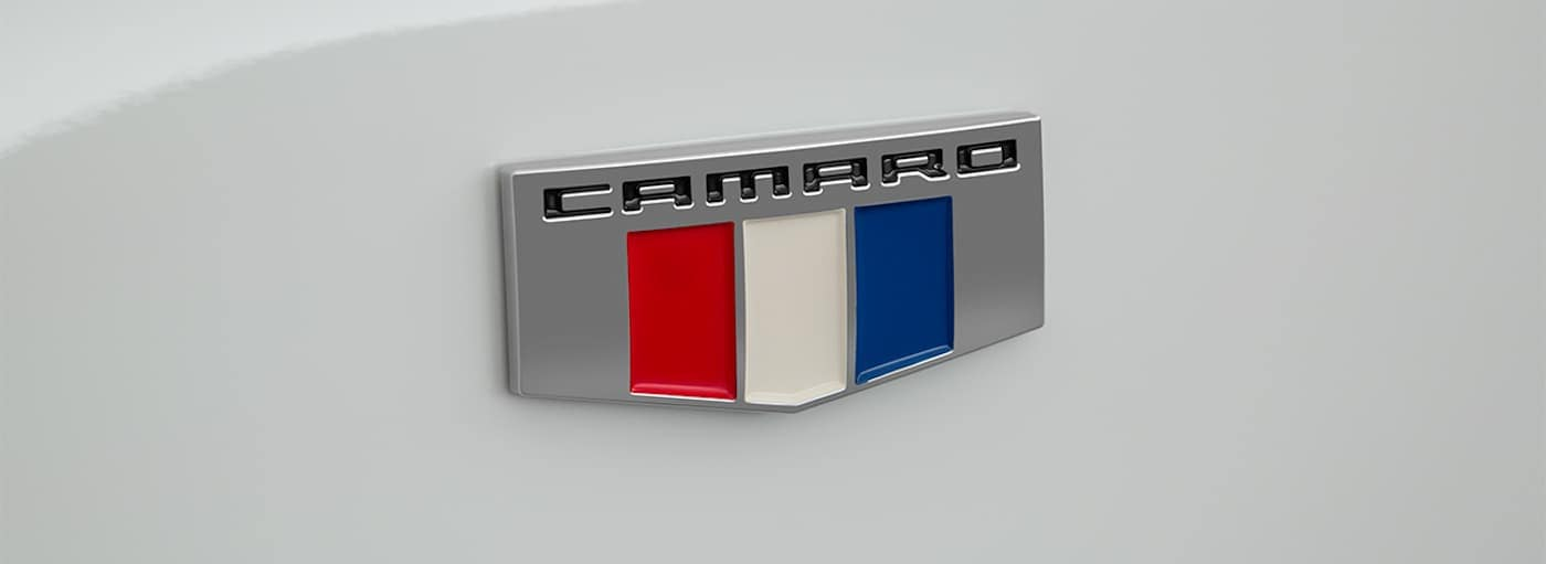 A closeup of the Camaro badging on a white 2019 Chevy Camaro is shown.