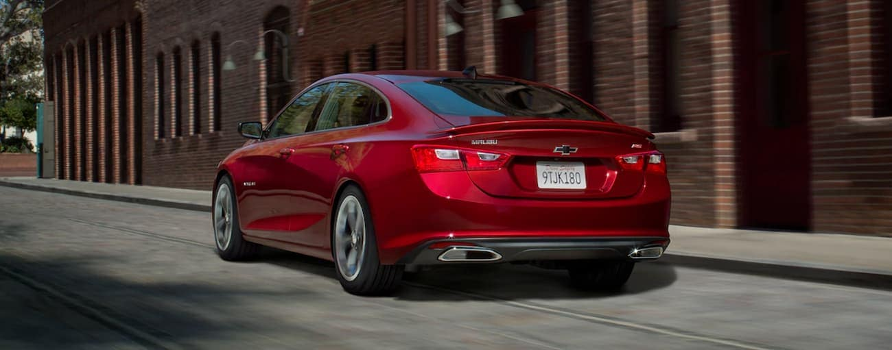 A red 2019 Chevy Malibu RS is driving past brick buildings.