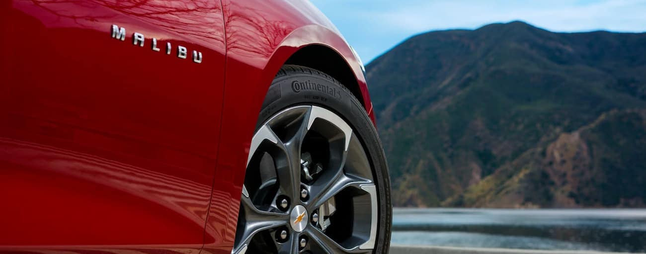 Th eMalibu badge is featured on the side of a red 2019 Chevy Malibu in front of a bay.