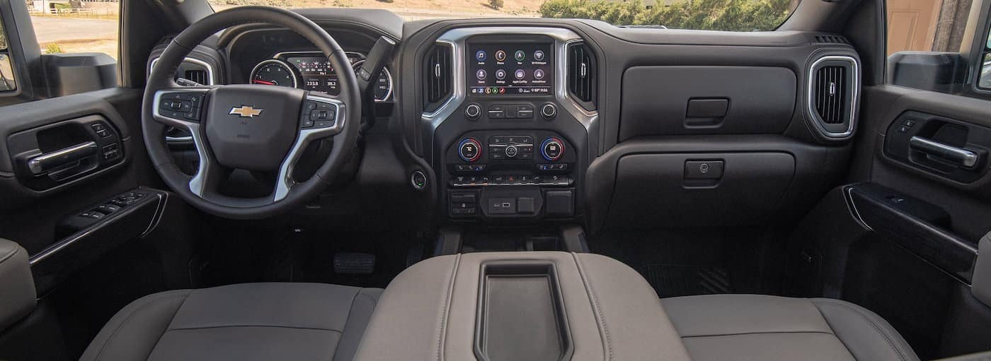 The front black leather interior of he 2020 Chevy Silverado 2500HD is shown with in infotainment system.