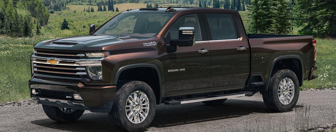 A brown 2020 Chevy Silverado 2500HD is parked on a dirt road with hills in the distance.