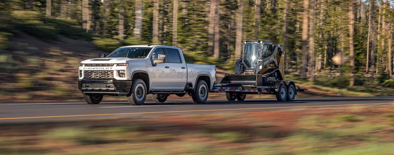 A white 2020 Chevy Silverado 2500HD is towing construction equipment.
