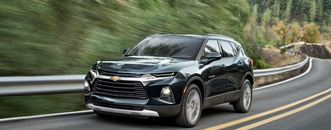 A black 2019 Chevy Blazer is driving on a winding road after leaving an Atlanta Chevy dealer.