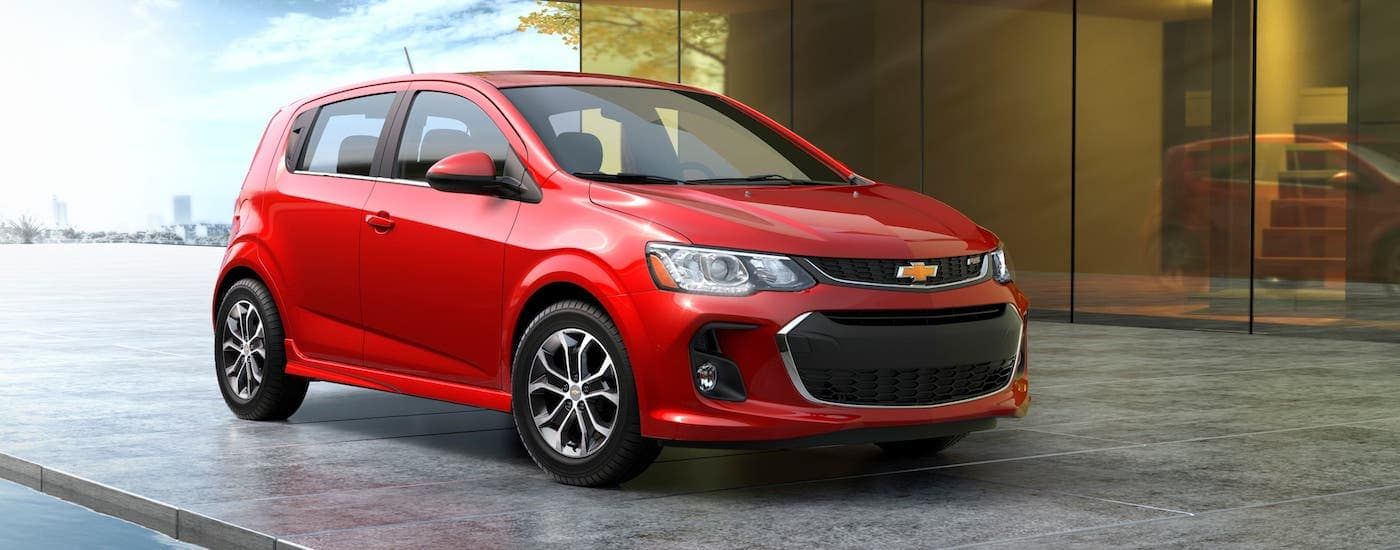 A red 2018 Chevy Sonic RS is parked in front of a modern home.