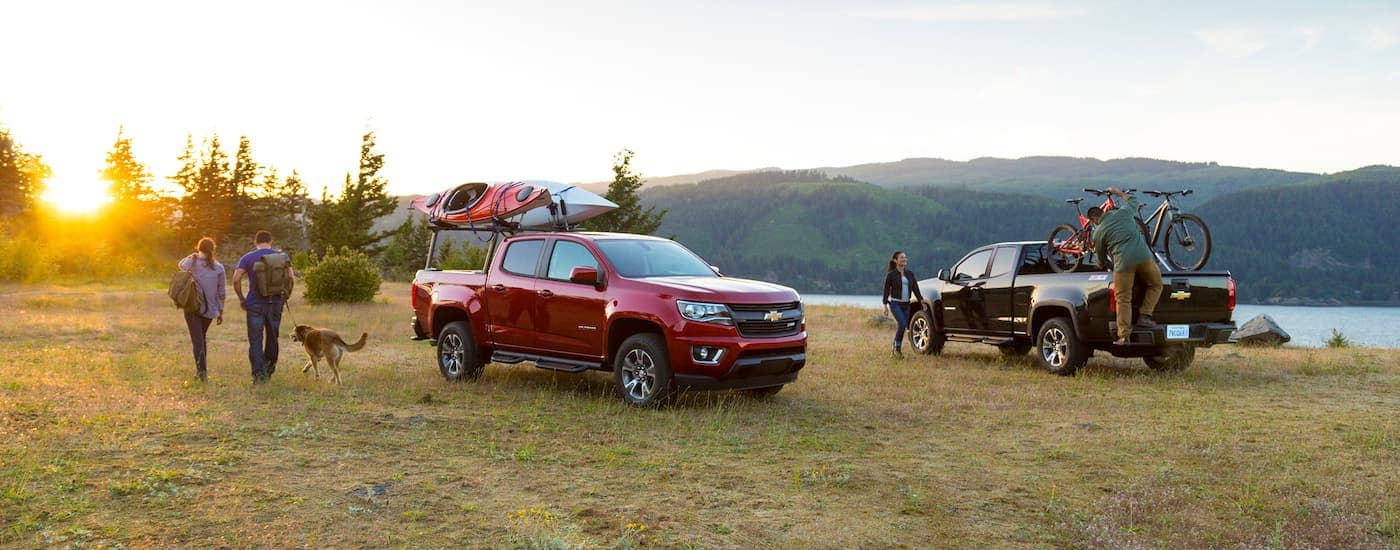 A red and a black 2015 Chevy Colorado are in a field with kayaks and bikes.