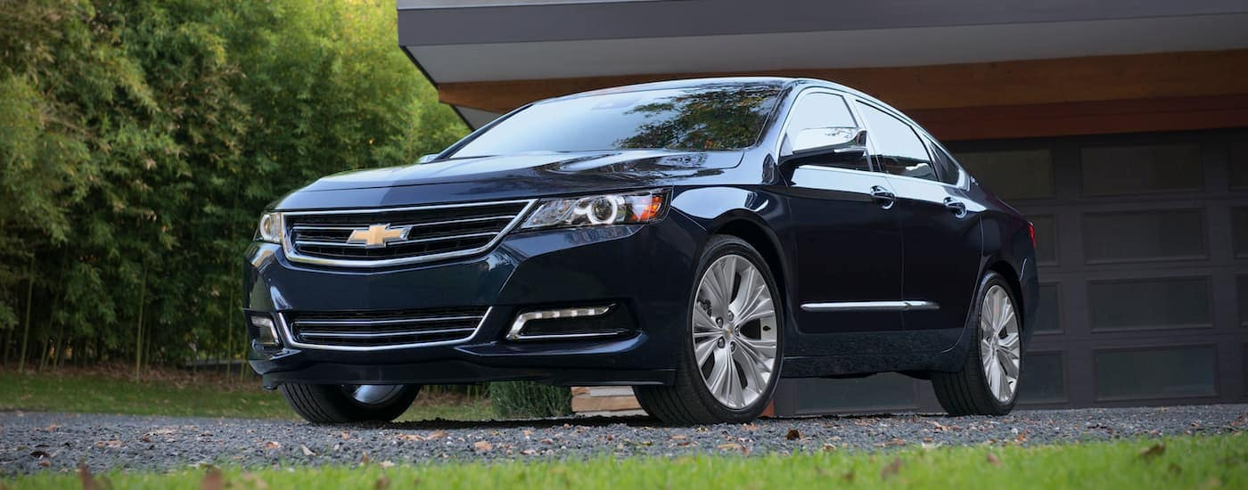 A dark blue 2015 Chevy Impala, a popular used Chevrolet car, is parked in a driveway near Buford, GA.