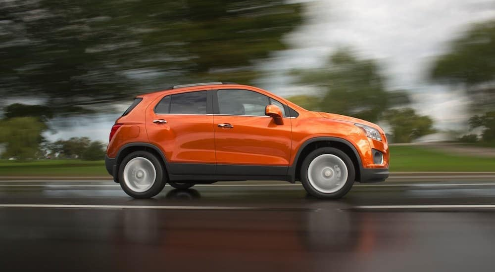 An orange 2016 Chevy Trax is driving in the rain near Buford, GA.
