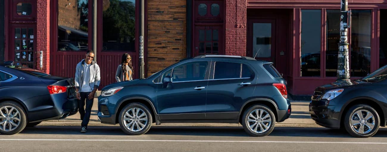 A couple is walking to their blue 2019 Chevy Trax parallel parked downtown.
