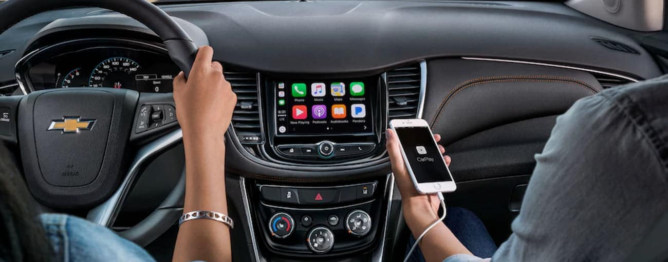 A passenger in a 2019 Chevy Trax is using the Apple Car Play feature.