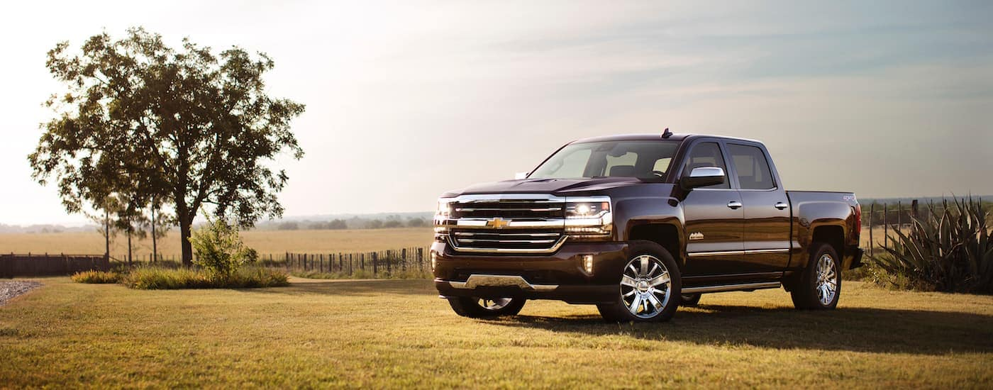 A dark colored 2017 Chevy Silverado is parked in a field.