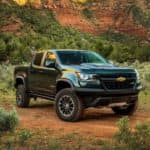 A black lifted 2018 Chevy Colorado, popular among lifted trucks for sale in Georgia, is parked in front of mountains.