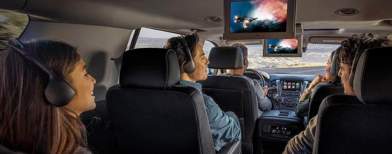 A family is in a 2020 Chevy Suburban with movies playing on the screens.