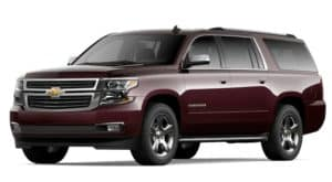 A burgundy 2020 Chevy Suburban is facing left.