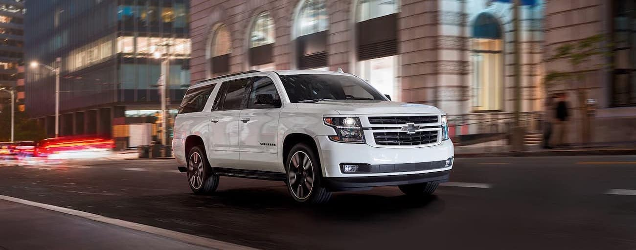 A white 2020 Chevy Suburban is driving downtown at night.