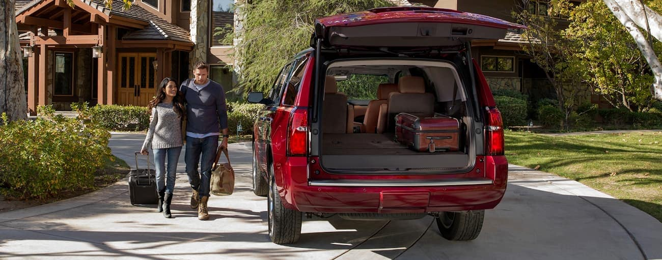 A couple is walking to their red 2020 Chevy Tahoe with luggage in the back at their home near Buford, GA.