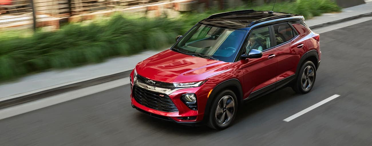 A red 2021 Chevy Trailblazer is driving on a highway past bushes near Buford, GA.