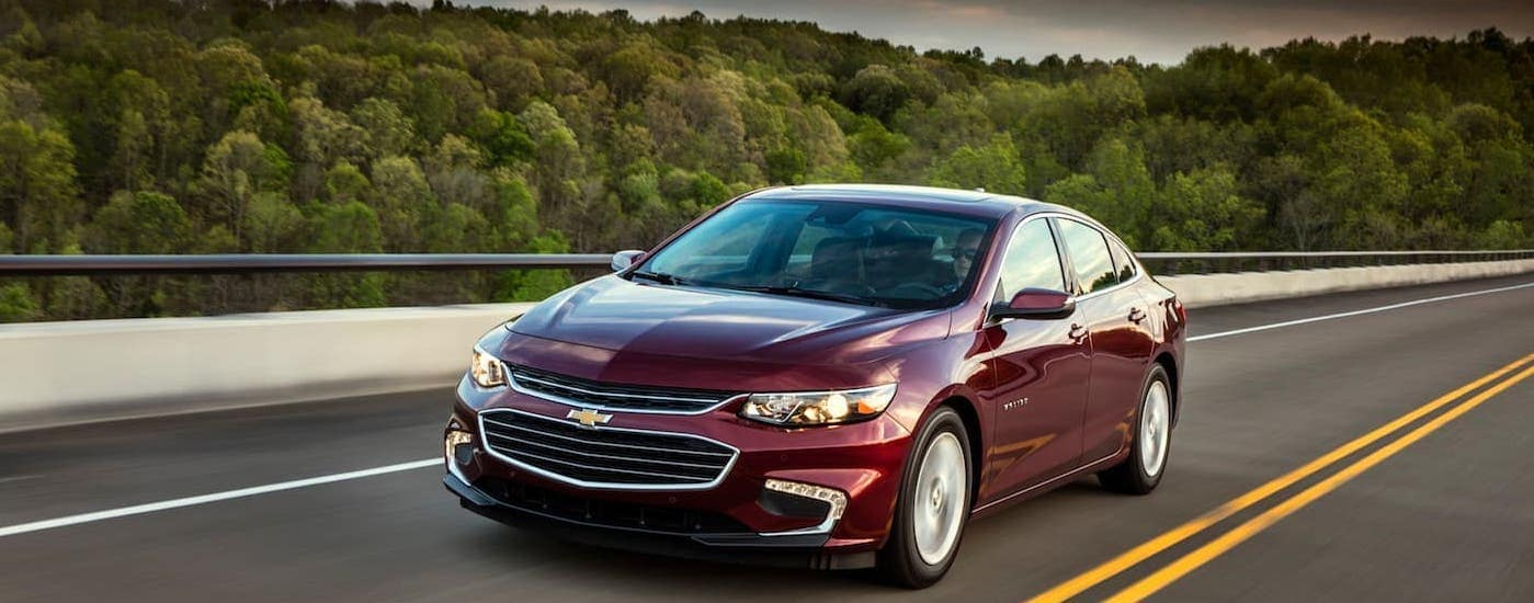 A red 2018 Chevy Malibu is driving on a highway near Atlanta, GA.