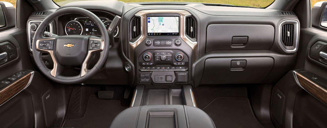 The front black leather interior is shown of a 2019 Chevy Silverado 1500 High Country trim parked in a field near Buford, GA.