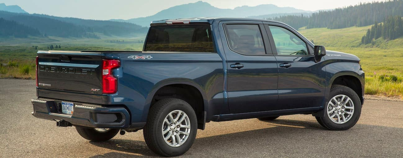 A dark blue 2019 Chevy Silverado 1500 is parked on a hill looking over mountains.