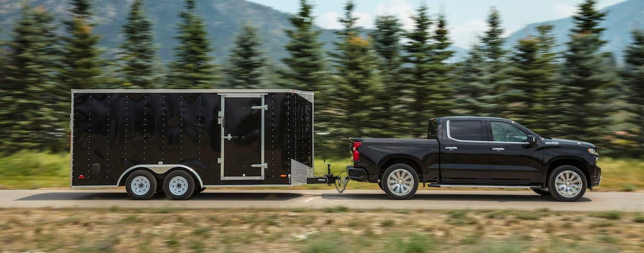 A black 2019 Chevy Silverado 1500, which wins when comparing the 2019 Chevy Silverado 1500 vs 2019 Ford F-150, is towing a large trailer.