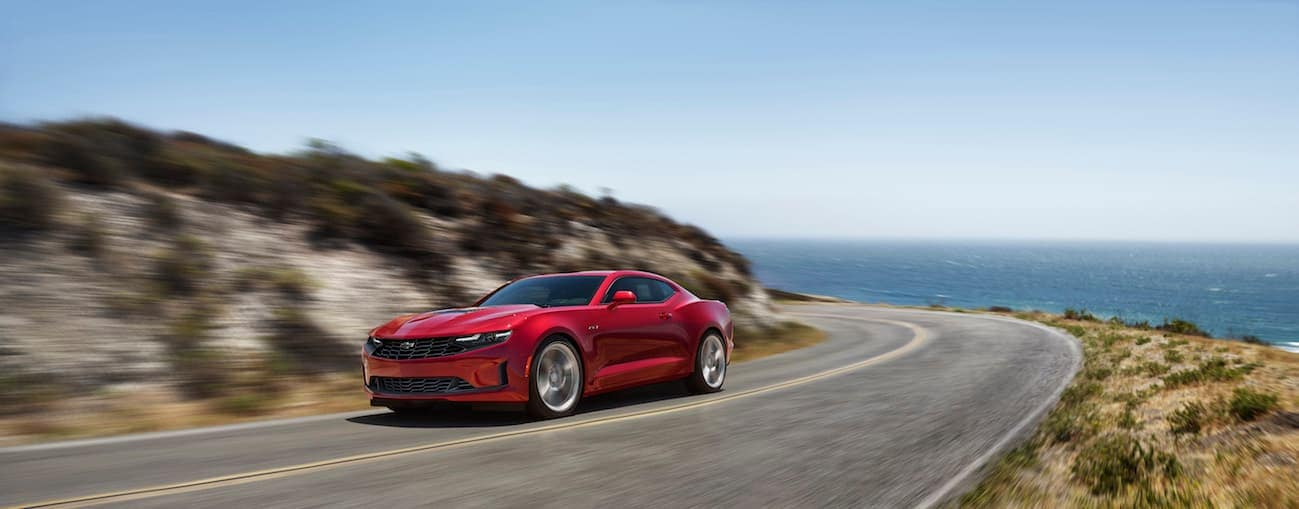 A red 2020 Chevy Camaro is driving near the ocean.