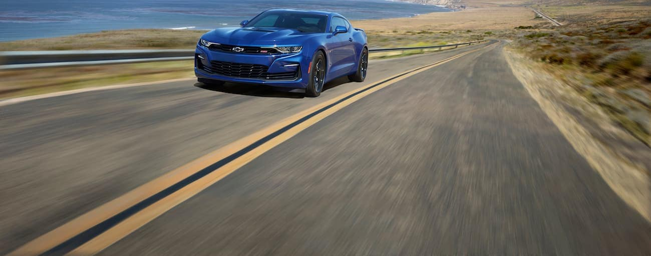 A blue 2020 Chevy Camaro is driving on a highway by the ocean.